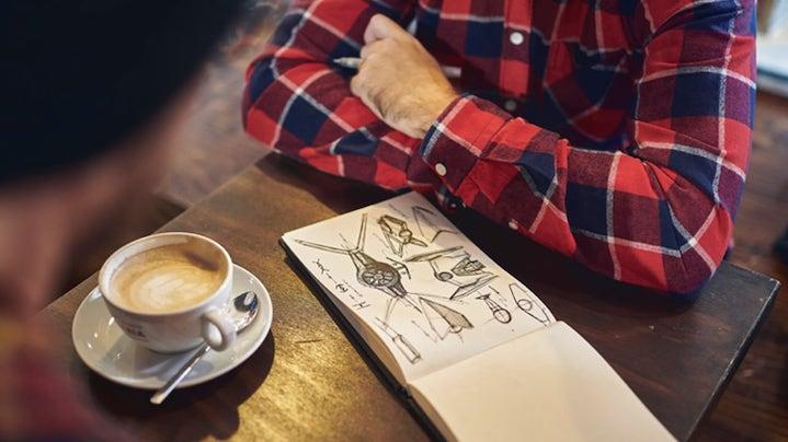 Moški pije kavo in skicira v zvezek