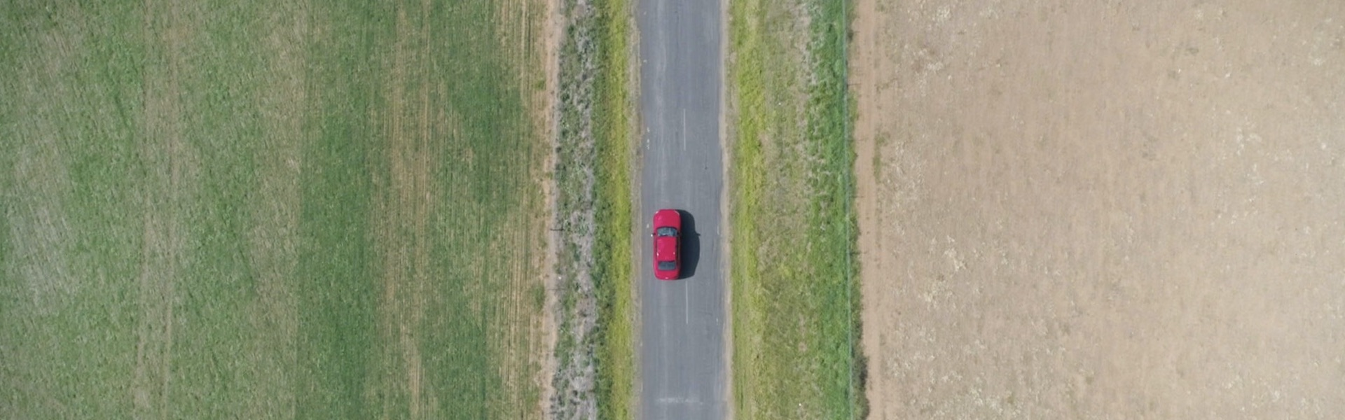 Audi na cesti med polji slikan od zgoraj