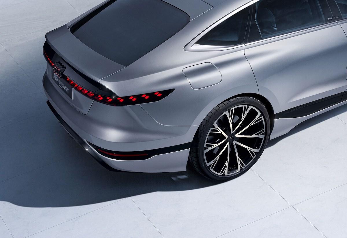 Stranski pogled na zadek vozila, ki poudarja moč quattro na kolesnih lokih in se pretvori v digitalni OLED-prikazovalnik.