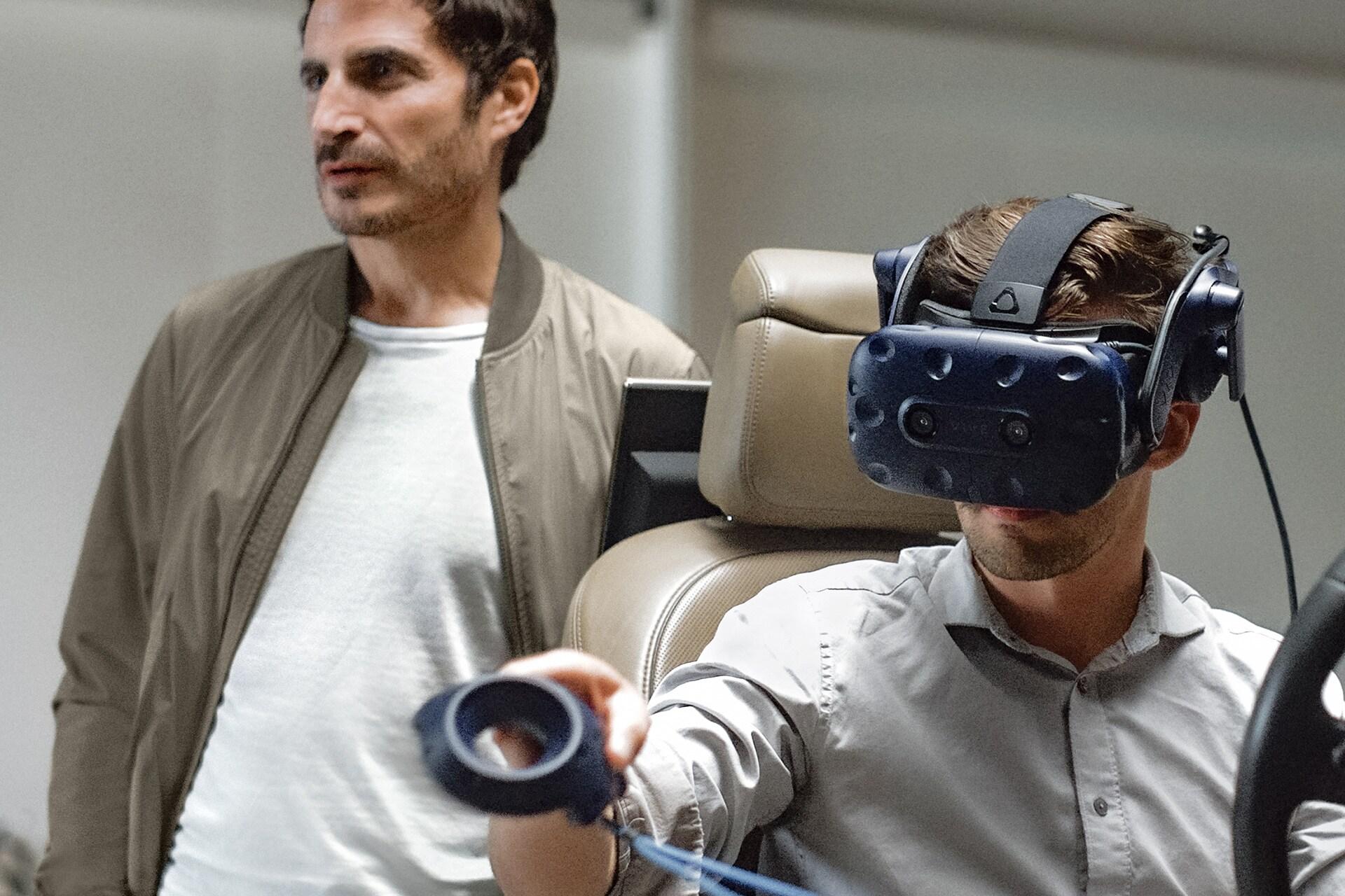 Gael Buzyn stoji za osebo z očali VR na avtomobilskem sedežu.