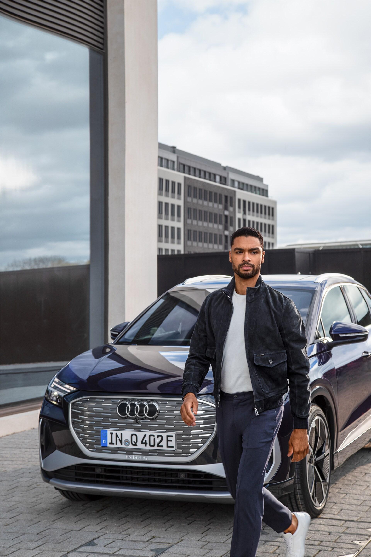 Regé-Jean Page se sprehaja ob povsem novem električnem modelu Audi Q4 e-tron.